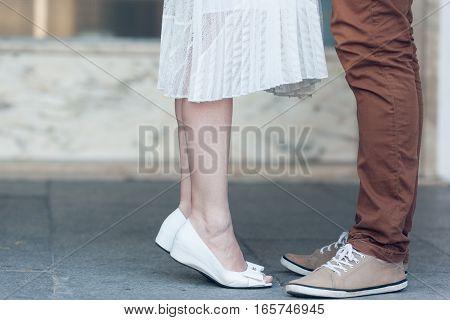 Girl stretches to kiss a her boyfriend0 closeup