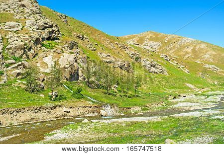 The narrow mountain river and tiny stream in rocky valley between Zarafshan and Gissar mountain ranges of Pamir-Alay the cows graze on the bank Uzbekistan.