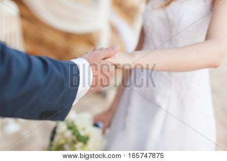 Groom holding bride's hand at ceremony closeup