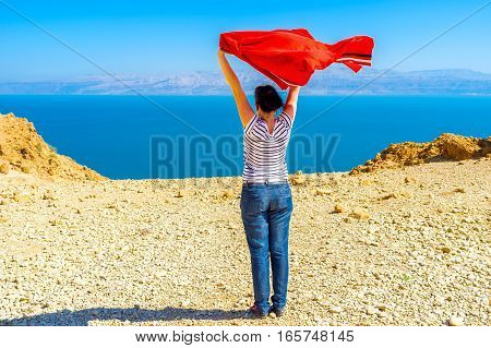 The girl enjoy the fresh air watching the Dead Sea standing on the mountain top in Judean Desert Ein Gedi Israel.