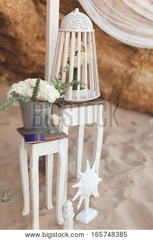 White wedding decorations on a table in the sand