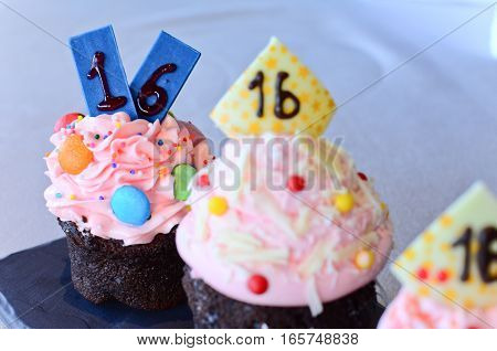 Closeup pink cupcake with number sixteen on top
