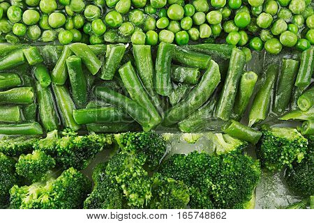 Assortment of fresh frozen green peas french bean broccoli with hoarfrost closeup as background. Healthy vitamin food.