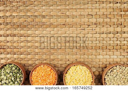 Assortment of lentils in a wooden bowls with copy space on bamboo mat background. Top view closeup. Healthy protein food.