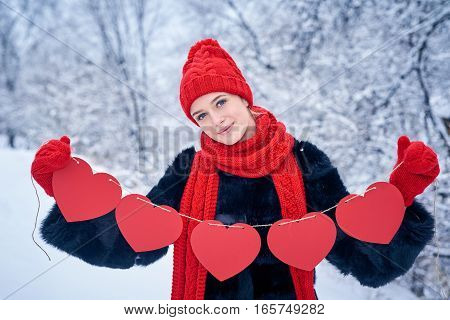 Love and valentines day concept. Smiling woman holding garland of five red paper hearts shape - blank copy space for letters or text, looking at camera over winter landscape