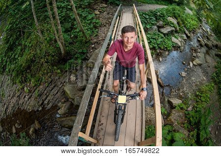 Man Rides A Bicycle Through Wooden Bridge Over A River