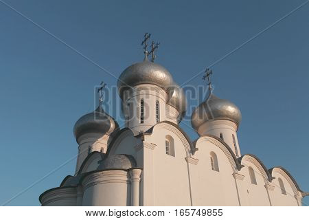 white church with silver domes against the blue sky