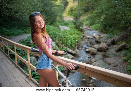 Female Standing With Bicycle On Wooden Bridge