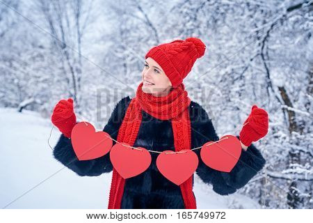 Love and valentines day concept. Smiling woman holding garland of four red paper hearts shape - blank copy space for letters or text, looking up over winter landscape