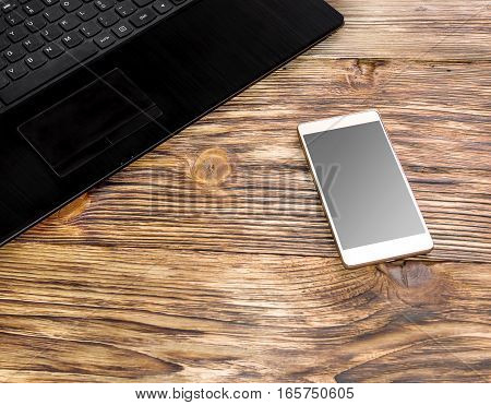 Smartphone and laptop on the wooden table.