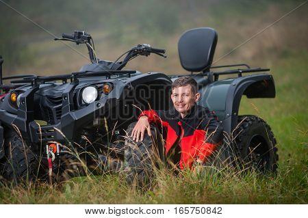 Young Man Sitting Near Four-wheeler Atv