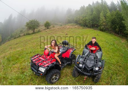 Happy Beautiful Couple Sitting On Four-wheelers Atv