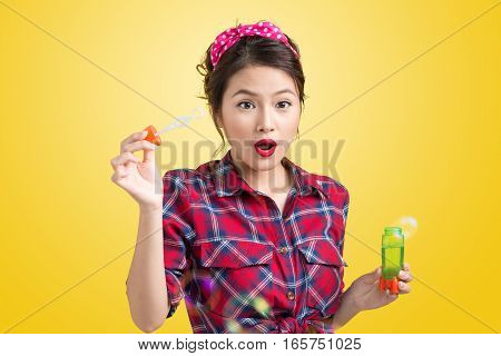 Pinup model blowing soap bubbles over yellow background.