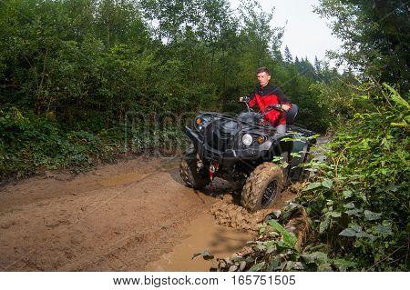Man Driving Four-wheeler Atv Through Mud
