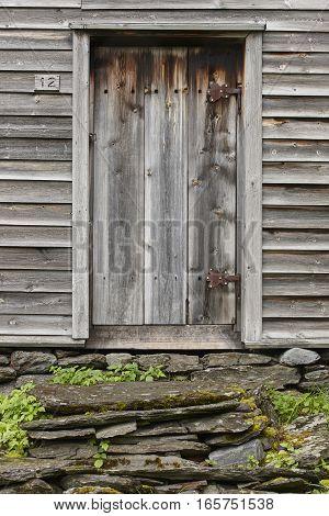 Wooden old rusty cabin door with stone stairway. Visit Norway