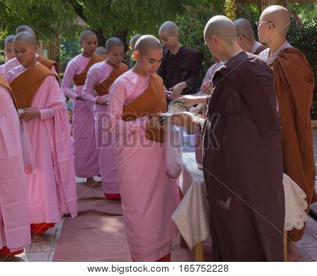 SAGAING MYANMAR - NOVEMBER 22 2016: Buddhist nuns are queueing holding their bowls to collect the unique daily meal at noon in the women monastery near Mandalay Myanmar (Burma).