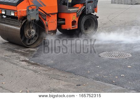 Road repair compactor lays asphalt. Repair pavement and laying new asphalt patching method outdoors.