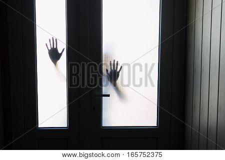 silhouette of hands outside the window door