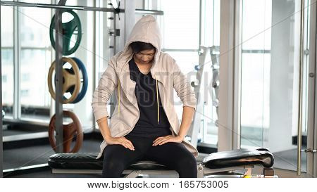 Asian Sportwoman Wearing Hood Tiring And Resting After Exercise At Gym