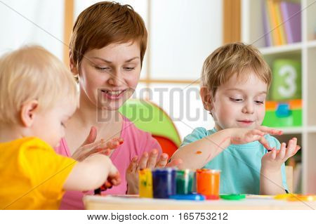 Kids boys with teacher painting in playschool
