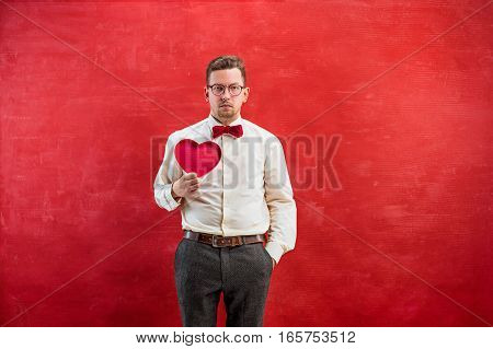 Young beautiful man with abstract heart on red studio background