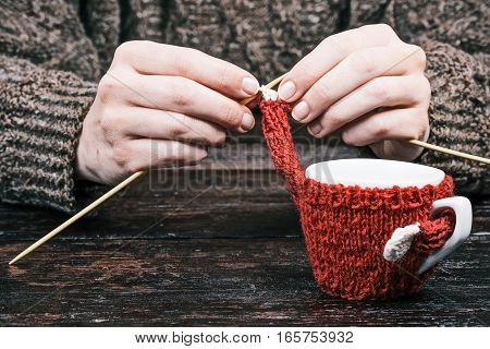 Human hands knitting the sweater for the coffee cup on the table