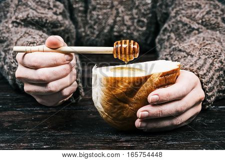 Human hands holding piece of wheat bread and spreading it with honey on dipper