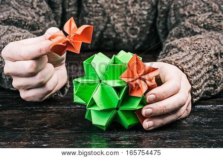 Human hands piecing flower kusudama on the table