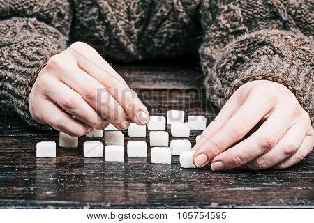 Human hands taking sugar cubes from the table