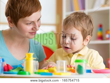 Kid with teacher play clay at home or kindergarten or playschool