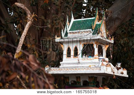 Thai religious green spirit house among trees for worshiping and offerings to gods. Small miniature Buddhist temple outdoors in the garden