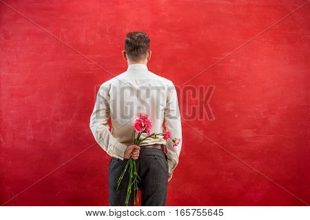Man holding bouquet of carnations behind back on red studio background