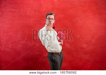 Young beautiful man with flowers on red studio background