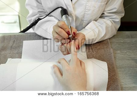 Finger nail care by manicurist to a girl client at beauty salon.