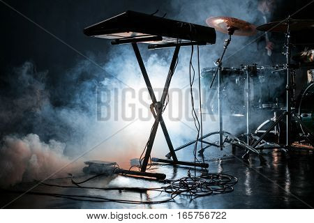 View of modern drum kit and electric piano in dark smoky studio