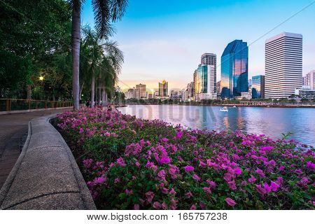 Cityscape photography of Benchakitti Park at twilight time in Bangkok, Thailand. Outdoor evening landscape of modern city skyscrapers in Asia