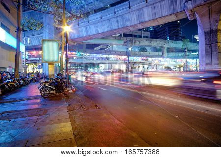 Night traffic lights of Bangkok highway with subway MRT line above the road and many scooters parked near the city center. Cityscape of the capital city of Thailand - Bangkok, Asia