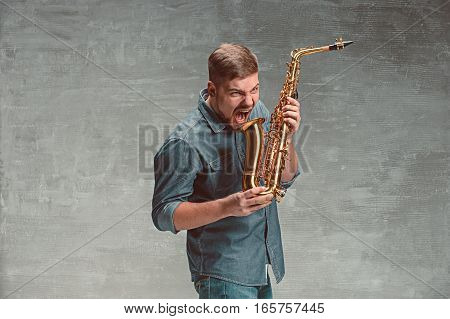 Happy saxophonist screaming at sax on gray studio background