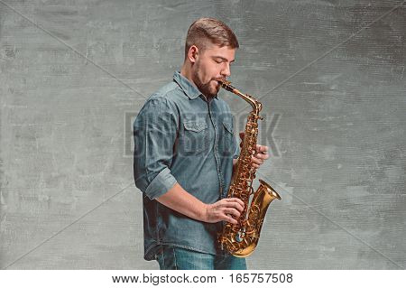Happy saxophonist playing music on sax on gray background