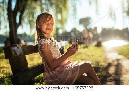 Portrait of a girl using a mobile phone in the park while sitting on a bench on a sunny day.
