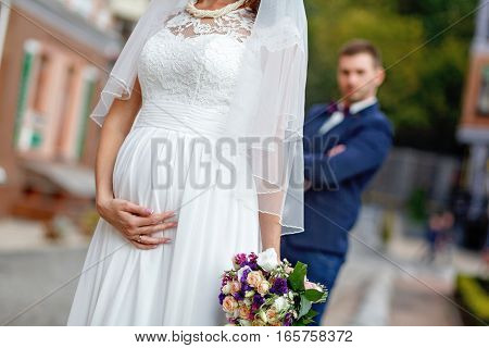 pregnant bride in lace veil holding a wedding bouquet. the groom in a tuxedo in the background
