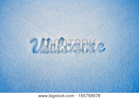 Welcome message imprint in the snow. Winter landscape.