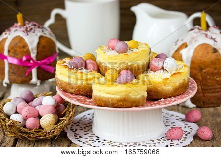 Easter nest cakes cheesecakes with colorful chocolate candy eggs on festive Easter table
