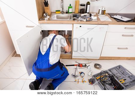 Male Plumber In Overall Repairing Sink Pipe In Kitchen