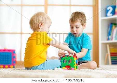 Kids toddler and preschooler boys play logical toy learning shapes and colors at home or nursery