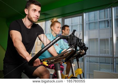 Young sportsmens on stationary bike at gym
