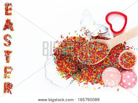 Easter baking ingredients - colorful sugar sprinkles cookie cutters paper tins for cake isolated on white background empty space for text top view