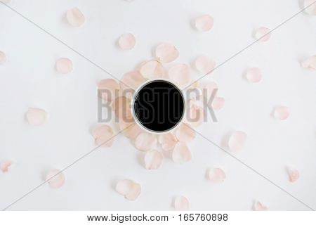 Coffee cup and pink roses petals pattern. Flat lay top view
