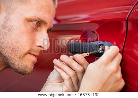 Close-up Of A Young Man Opening Car Door With Lockpicker