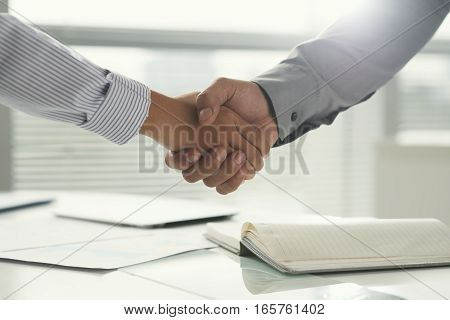 Close-up image of coworkers shaking hands after successful meeting